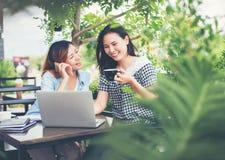 享受的两个朋友面带笑容在咖啡店 免版税库存图片