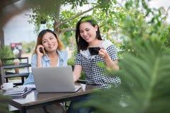 享受的两个朋友面带笑容在咖啡店 免版税库存照片