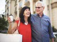 享受的成熟夫妇多跑一些商店比较价格的高低 免版税库存照片