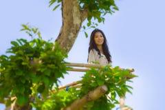 享受看法从在树微笑的高观点的年轻美丽的亚裔韩国妇女画象愉快和轻松在holida 图库摄影