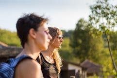 享受看法的两个美丽的女孩,戴太阳镜 免版税库存图片