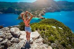 享受看法的少妇对从顶面城堡的Assos村庄Kefalonia 美丽的蓝色色的海湾盐水湖在底下 库存图片