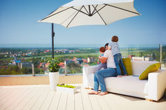 享受看法的愉快的家庭,放松在长沙发在屋顶上面大阳台温暖的晴天 图库摄影