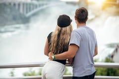 享受看法的愉快的旅游夫妇对尼亚加拉瀑布在浪漫假期时 看对自然的人们环境美化在日落蒂姆 免版税库存图片