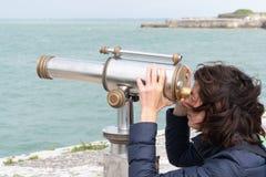 享受看法的美丽的深色的妇女由投入硬币后自动操作的双筒望远镜沿海 免版税库存图片