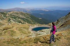 享受看法的远足者在湖附近 库存图片