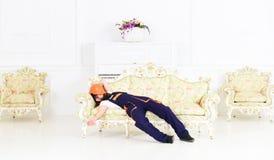享受短的休息的疲乏的人在工作 说谎在沙发的有胡子的搬家工人在有钢琴和葡萄酒家具的绝尘室 库存照片