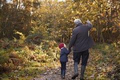 享受秋天步行的祖父和孙女 免版税库存图片