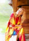 享受秋天的正面妇女,包裹在温暖的毯子 库存照片