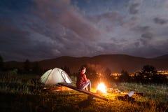 享受篝火的妇女在帐篷附近在多云天空下 免版税库存照片