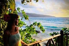 享受美好的热带日落的少妇 免版税库存照片