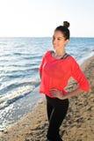 享受美好的晴天的年轻微笑的妇女,当站立在海滩在夏天时 库存图片