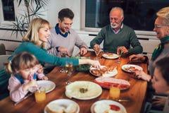 享受膳食的多一代家庭在桌附近 免版税库存图片