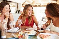 享受膳食的小组女性朋友在室外餐馆 库存图片