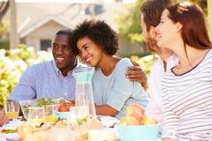 享受膳食的小组朋友在室外党在后院 库存照片