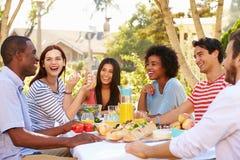 享受膳食的小组朋友在室外党在后院 免版税库存照片