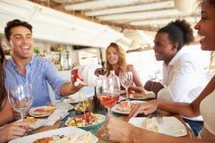 享受膳食的小组年轻朋友在室外餐馆 免版税图库摄影