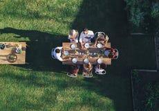 享受膳食的朋友在室外党在后院 库存图片