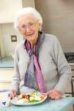 享受膳食的高级妇女在厨房里 免版税库存图片