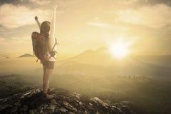 享受自由的女性背包徒步旅行者在山 免版税库存照片