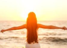 享受自由的自由的妇女感到愉快在海滩在日落 是 免版税图库摄影