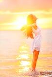 享受自由的自由的妇女感到愉快在海滩 免版税库存图片