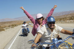享受自行车乘驾的四个朋友 免版税库存照片