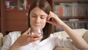 享受舒适在家平衡的妇女 单独饮用的白兰地酒的科涅克白兰地开心 酒精中毒概念 股票录像