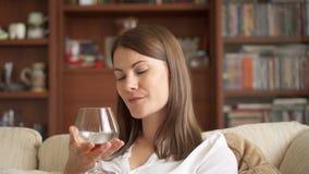 享受舒适在家平衡的慢动作妇女 单独饮用的白兰地酒的科涅克白兰地开心 影视素材