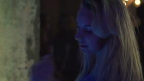 享受舞蹈和演奏金发的诱人的女性在夜总会,慢mo 影视素材