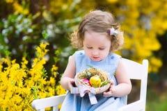 享受蛋狩猎的可爱的小孩女孩在庭院里 免版税库存照片