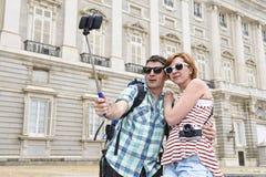 享受西班牙假日的年轻美国夫妇绊倒采取selfie与手机的照片自画象 库存照片