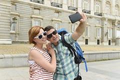 享受西班牙假日的年轻美国夫妇绊倒采取selfie与手机的照片自画象 免版税图库摄影