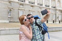 享受西班牙假日的年轻美国夫妇绊倒采取selfie与手机的照片自画象 图库摄影