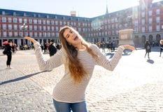 享受西班牙观光的可爱的愉快的年轻女人在马德里 在旅游业方面在欧洲城市 库存照片