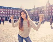 享受西班牙观光的可爱的愉快的年轻旅游妇女在马德里欧洲市 库存照片