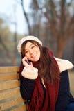 享受谈话在长凳的手机的女孩在公园 库存图片