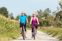 享受退休的活跃资深夫妇,当乘坐骑自行车i时 免版税库存照片
