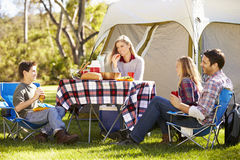 享受野营假日的家庭在乡下 免版税库存图片