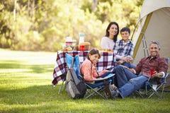 享受野营假日的家庭在乡下 免版税库存照片