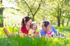 享受野餐的家庭在开花的庭院里 免版税图库摄影