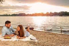享受野餐的年轻夫妇在海滩 说谎在野餐毯子 游泳背景的白色天鹅 免版税库存图片