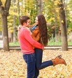 享受金黄秋天的愉快的夫妇画象  免版税图库摄影