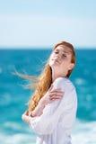 享受阳光的妇女在海滩 免版税库存图片