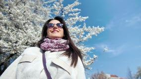 享受阳光的微笑的美女在有白色开花的佐仓树和天空蔚蓝的春天庭院 股票录像