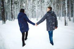 享受降雪的快乐的人和俏丽的女孩室外后面看法画象在冬天森林里 免版税库存图片
