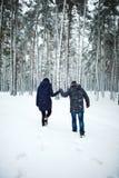 享受降雪的快乐的人和俏丽的女孩室外后面看法画象在冬天森林里 免版税库存照片