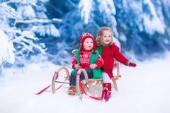 享受雪橇乘驾的孩子在圣诞节 免版税库存图片