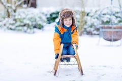 享受雪橇乘驾的小孩男孩在冬天 免版税库存图片