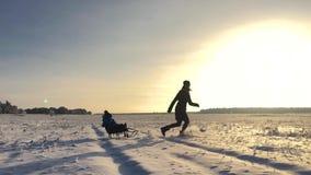 享受雪橇乘驾的小男孩 母亲雪撬他逗人喜爱的孩子 家庭户外冬天活动 有愉快的家庭 股票录像
